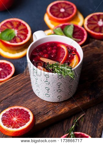 Mulled wine with slice of red orange, fresh rosemary and spices. Glass with hot drink
