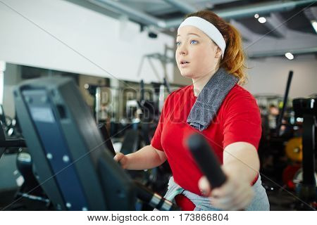 Portrait of cute overweight woman with red hair working out using machines in gym to lose weight