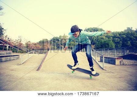 young skateboarder practice ollie at skatepark ramp