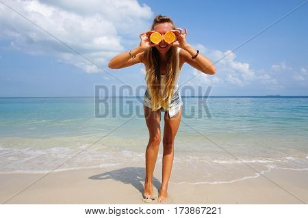 Pefect Vacation Concept. Summer travel. Young beautiful funny model holding orange in front eyes with smile relaxing on the beach in sunny day