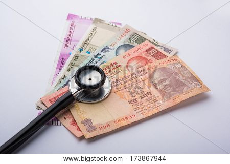 Stethoscope on indian money or paper currency background - medical or business concept