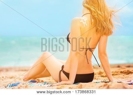 Young girl with suntan lotion having rest near seacoast. summer concept