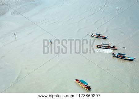 Top view of traditional thai fisherman longtail boat in the blue sea in Khao Sam Roi Yot National Park, Thailand. Aerial view of turquoise clear sea water and tourists walking from longtail boats