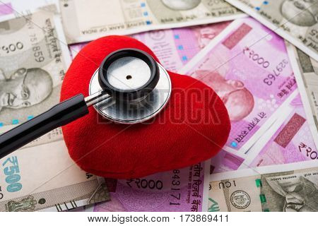 affordable Heart care in India - concept showing crashed price of angioplasty stents, stethoscope examining a red colour toy /stuffed heart with new currency notes of rupees 2000, 500 in background
