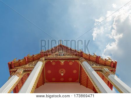 Traditional red roof with gold ornament of Chinese style temple bottom view with sunny blue sky in Bangkok, Thailand. Oriental buddhist architecture in Asia