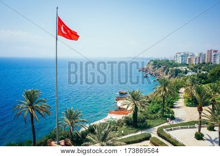 Beautiful marine panorama of mediterranean summer nature with palm trees, bright sun, warm sea and clean blue sky in Antalya with flag of Turkey. The rocky coast of Antalya. Turkey - travel background