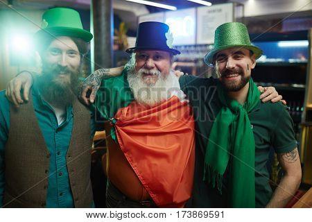 Three happy buddies in Irish costumes in pub