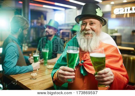 Senior man in hat holding two glasses of beer