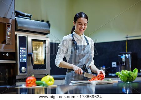 Apprentice of chef cutting ingredients for salad