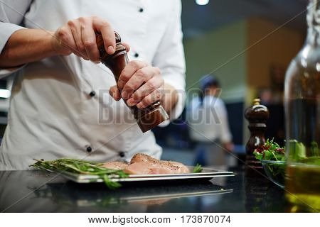 Man in uniform of chef seasoning lean meat with spices