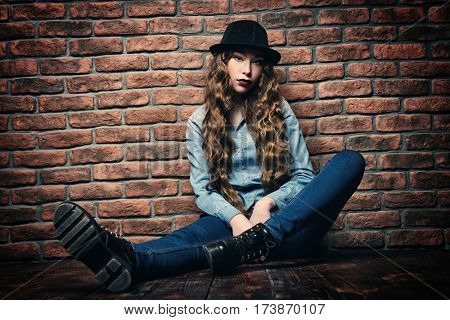 Attractive young woman sitting on a floor by the brick wall. Hipster girl. Youth fashion, beauty. Long hair, haircare.
