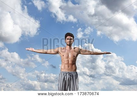 Muscular young man standing with arms wide open against cloudy sky