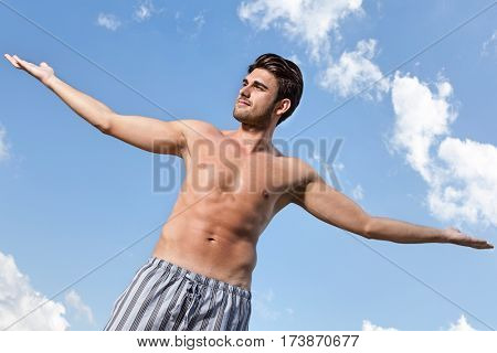 Muscular young man standing arms outstretched against cloudy sky