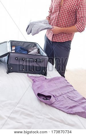 Midsection of young businessman unpacking luggage in hotel room