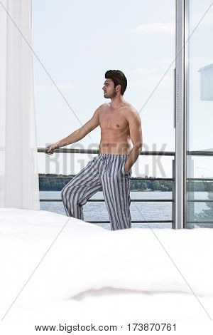 Shirtless young man on hotel balcony looking away