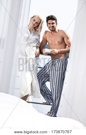 Portrait of happy young couple in sleepwear having coffee at hotel balcony