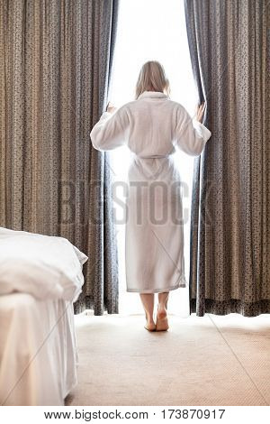 Full length of young woman in bathrobe opening bedroom curtains at hotel room