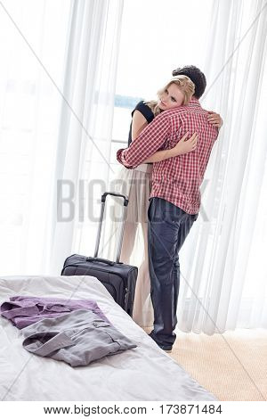 Loving young couple hugging in hotel room