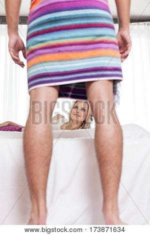 Young woman looking at man wrapped in towel at hotel room
