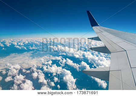 The wing of the aircraft above the clouds