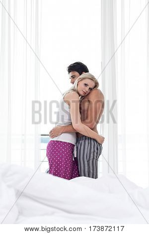 Side view of young couple hugging in hotel room