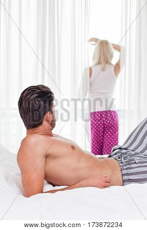 Young man looking at woman standing by window in hotel room