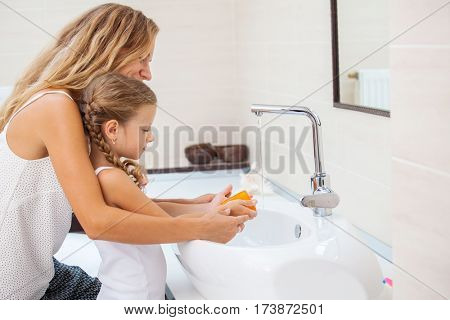 Mother and daughter washing their hands. Female with a child to wash their hands with soap and water