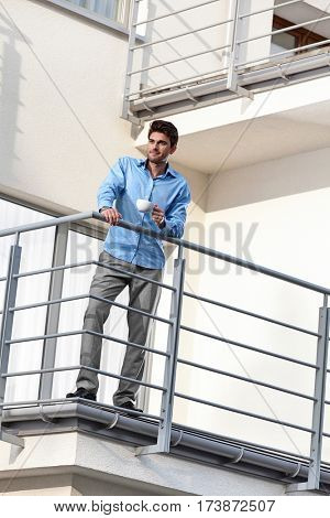 Full length of young businessman having coffee at hotel balcony