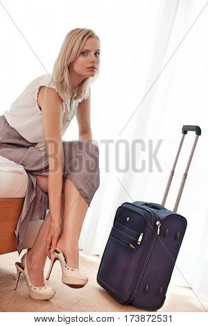 Portrait of beautiful young businesswoman removing high heels in hotel room