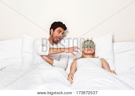 Angry young man teasing sleeping woman in bed
