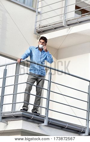 Full length of young businessman drinking coffee at hotel balcony