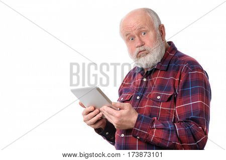 Senior bald and bearded white haired man doing something with tablet computer, isolated on white background