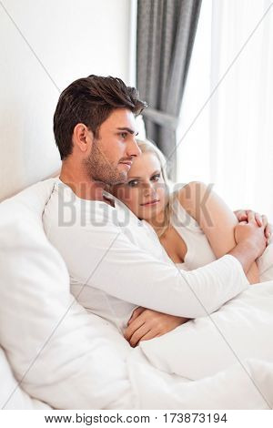 Portrait of young woman with man hugging in hotel room