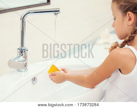 Child washes his hands at bathroom. Girl washing hand with soap