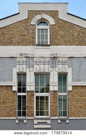 Beige brick wall in Art Nouveau style with high windows and decorative elements. Slonim, Belarus.