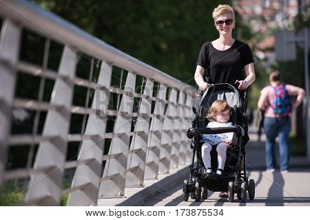 beautiful young mother with blond hair and sunglasses pushed her baby daughter in a stroller on a summer day