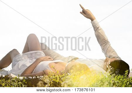 Young man lying with girlfriend while pointing against clear sky