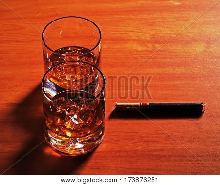 Highball whiskey glass with ice and cigar on wooden background. Close up.