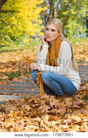 Full length of thoughtful young woman crouching on steps in park