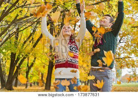 Couple enjoying falling autumn leaves in park