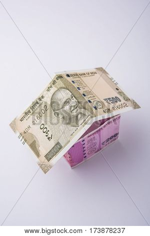 currency paper home or model house created using indian new 2000 and 500 rupee notes - India and real estate concept, selective focus, isolated