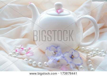 white kettle , beads and flowers on a cream background