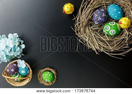 Top view Easter background.Happy easter eggs pained on nest also beautiful flower.Texture balck wooden with decorations and copy space.