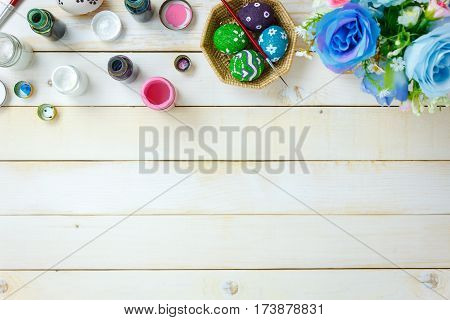Top view accessories happy Easter festival background.Preparation items handmade painted cute easter eggs for chil on rustic white wooden and decoration beautiful flower color with copy space.