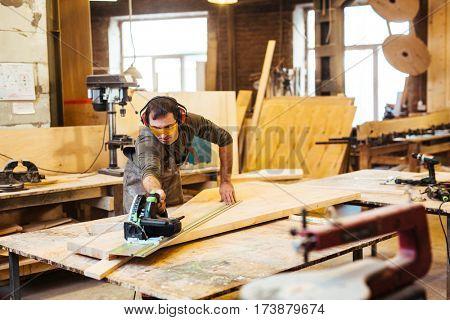 Woodworking artisan cutting wooden plank