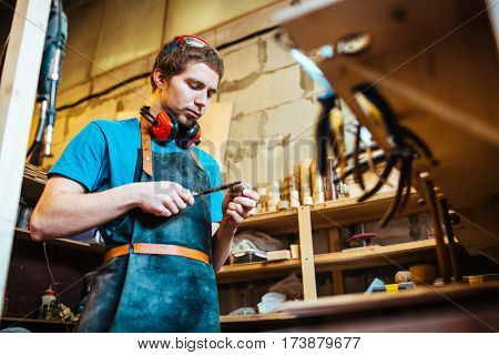 Young cabinetmaker processing wooden detail with chisel