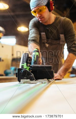 Man working with electric scroll-saw in workshop