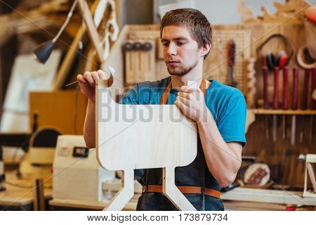 Self-employed cabinetmaker processing plank in his workshop