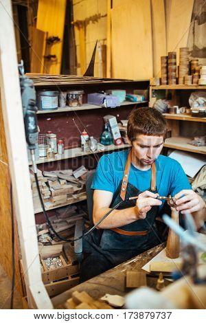 Cabinetmaker finishing wooden workpiece or detail