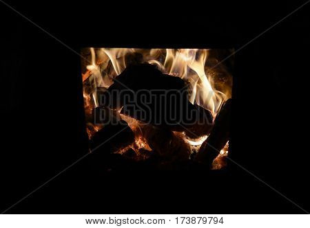 burning wood and the flames in the hearth of the fireplace